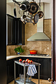 Compact kitchen with matt black lacquer cupboards and Corian worktops, cooking pots hang from the ceiling above a kitchen trolly