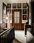 Early 20th century photographs on landing with velvet pile carpet, plaster bust of George Washington and glass panelled door