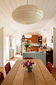 Marble-topped base unit painted blue and oak dining table in open-plan kitchen-dining room