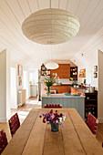 Offene Küche mit Essbereich, Esstisch aus Eichenholz, darüber Hängelampe mit Papierschirm