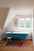 Free-standing bathtub, Moroccan rug and wooden stool in rustic bathroom