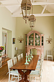 Old French farmhouse table in dining room with Swedish style chairs and antique French cupboard