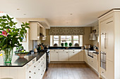 White units with black granite worktops in stylish kitchen with decorative confit jars