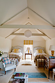 Attic twin bedroom with beamed ceiling, yellow striped matching blinds and cushions and blue armchairs