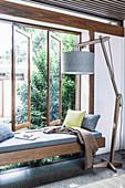 Holz-Stehleuchte und eingebaute Sitzbank vor Fenster