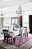 A laid dining table under a candlestick in a converted barn