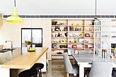 Kitchen counter and dining area with gray upholstered chairs in front of an open shelf