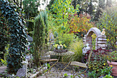 Seating area in autumnal garden with romantic metal furniture