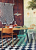 Dining table with various chairs, macrame wall hanging above