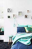 Bed with bedclothes in aqua tones, shelving set above, pendant lamp and stool as bedside table