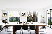 Wooden dining table with black chairs in a bright living room