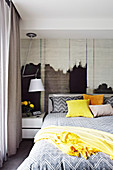 Double bed, bedside table and lamp in the bedroom with textile wallpaper on the wall