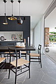 Black dining table and chairs in front of partition wall and next to open terrace doors