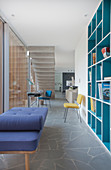 Turquoise fitted shelving and couch next to glass sliding door in open-plan interior