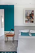 Double bed with grey headboard and side table in bedroom with turquoise wall cladding