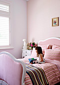 Girl sitting on bed with pink bedding in girl's room