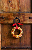 Small Christmas wreath with ribbon decorating door