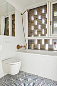 Shower head over bathtub, mirror, and toilet in bathroom in bathroom with window behind perforated brick façade