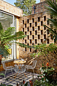 Outdoor furniture on tiled terrace against perforated brick wall
