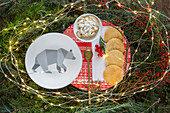 Plate with bear motif and biscuits in nest of conifer branches and fairy lights