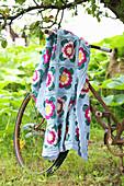 Geblümte Häkeldecke hängt überm rostigen Fahrrad im Garten