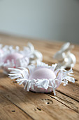 Easter eggs in handmade paper nests on wooden surface
