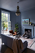 Sofa in front of open fireplace in classic grey living room