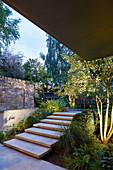 Treppe zur Terrasse im Garten mit verschiedenen Ebenen am Abend
