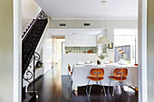 Laid dining table with classic chairs, side stairs with wrought iron railings