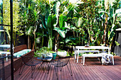 Wooden terrace with outdoor furniture, surrounded by tropical plants