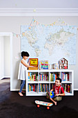 Girl and boy in children's room with bookshelf and map on wall