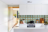 White fitted kitchen with colored tiles as splash protection