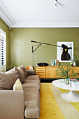 Sofa, sideboard and classic table in the living room with green walls