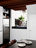 Stainless steel fridge combination in white kitchen, dining table in the foreground