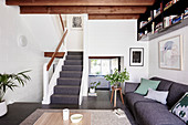 Gray upholstered sofa in the living room with beamed ceilings and stairs
