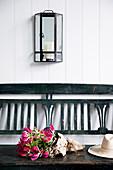 Antike Wandlaterne aus Messing und Glas über Holzbank mit Gloriosa
