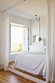 Double bed with white blanket on pedestal in the sleeping area with white curtain