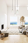 Upholstered furniture and carpet in front of fireplace in white living room with sea view