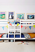 Two bunk beds decorated with a pennant chain and pictures on the wall in the children's room