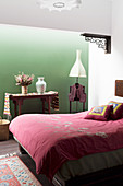 Double bed in the bedroom with green wall