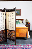 Screen with Chinese characters in front of a vintage wooden double bed