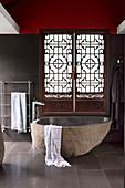 Basalt bathtub and ornate antique shutter in designer bathroom