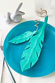 Turquoise felt feathers on blue plate