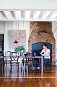 Dining area in front of rustic fireplace, woman with laptop at the table