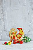 Old toy cockerel and Easter decorations against grey wall