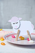 Lamb made from paper and clothes pegs on plate