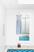 Sommerkleid an Wandspiegel, blauer Teppich und Kleiderschrank in weißem Schlafzimmer