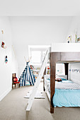 Bunk bed with bed ladder in white children's room, teepee in background