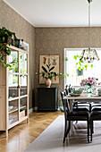 Gedeckter Tisch im Esszimmer mit Vitrinenschrank und Vintage-Tapete