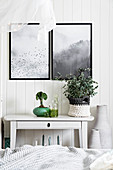 Pictures above green ornaments on side table in white bedroom